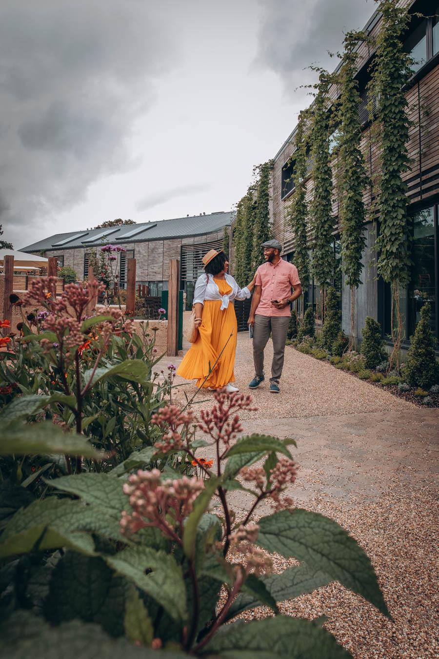 Couple walking by Wellbeing Garden behind RHS Hilltop   RHS Garden Wisley