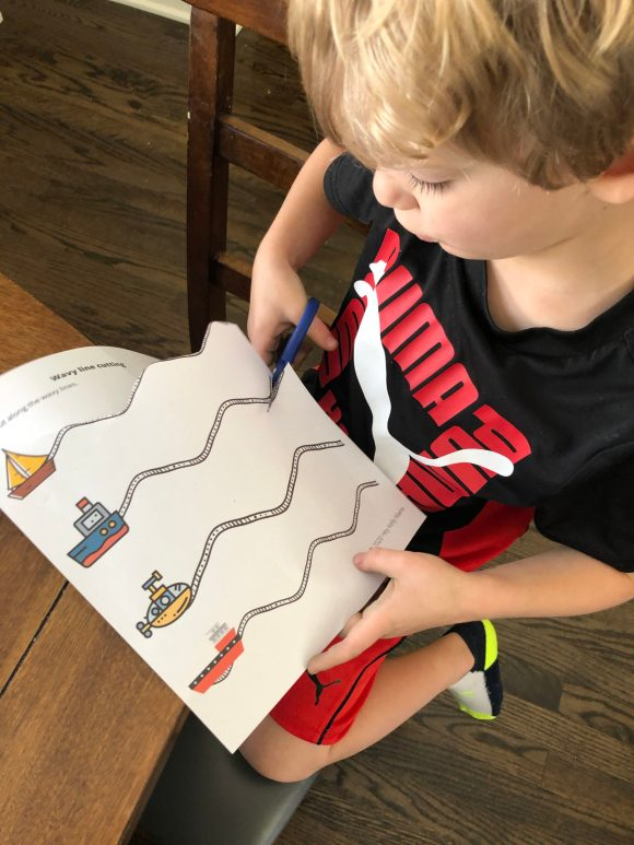 Boy practicing cutting wavy lines, one activity in the free preschool cutting workbook.