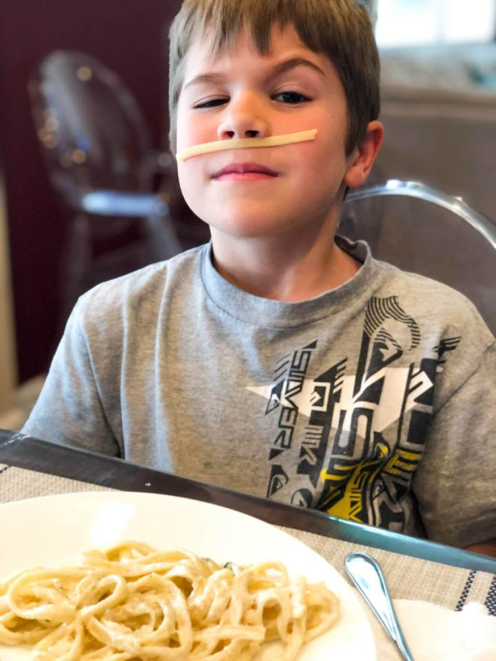young boy with noodles on his face eating dinner