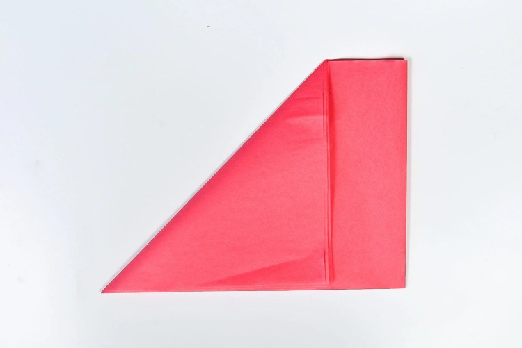 Find the corner with all of the separate pieces of paper (not one with a fold). Take this corner and fold it to the opposite edge to make a triangle.