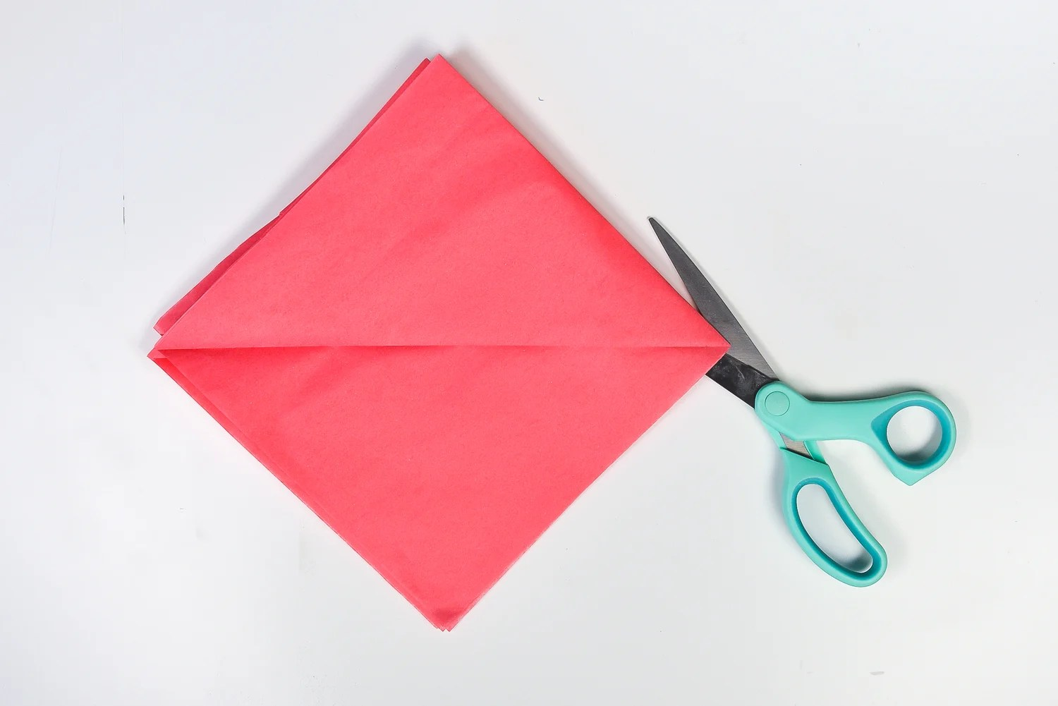 How to Make Tissue Paper Flowers: Cut folded edge to separate all 8 pieces of tissue paper.