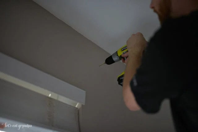 man drilling hole in wall to hang curtains