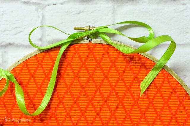 green ribbon tied to top of orange pumpkin embroidery hoop