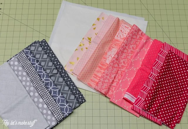 various fabric squares in red, gray, pink and black on sewing mat