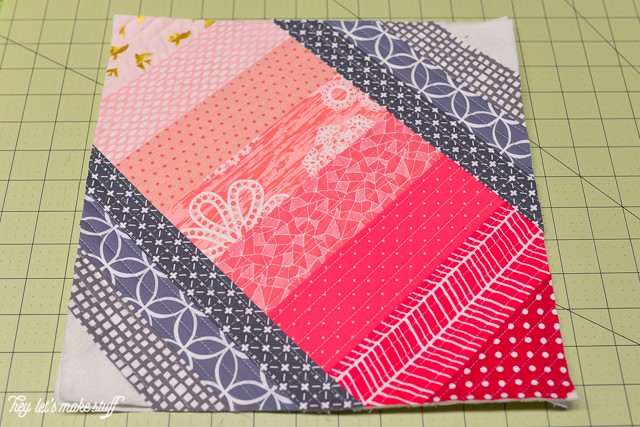 fabric layered all the way down with fabric strips on side on batting on sewing mat