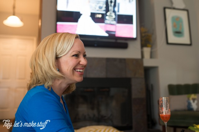woman smiling and watching Oscars