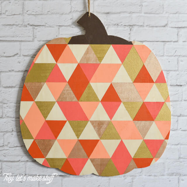 finished geometric painted pumpkin hanging on white brick fireplace