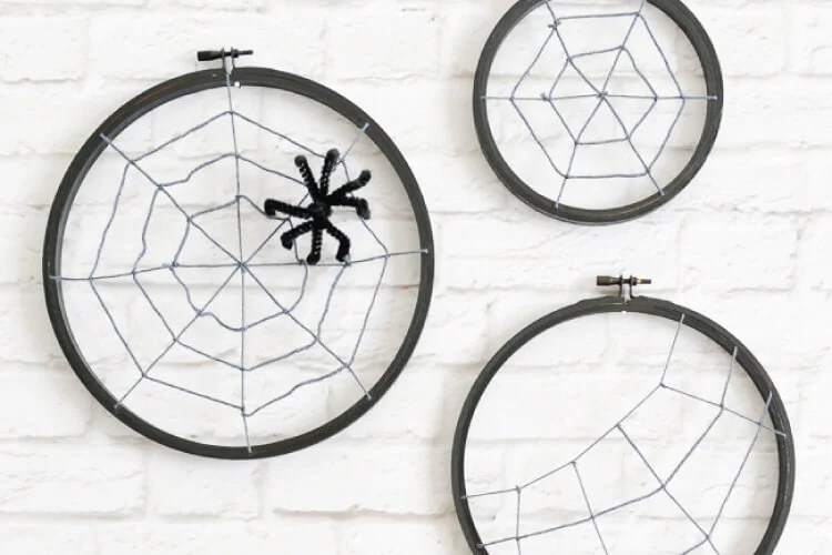 Turn some simple craft supplies—yarn and an embroidery hoop—into spooky Halloween spider hoops!
