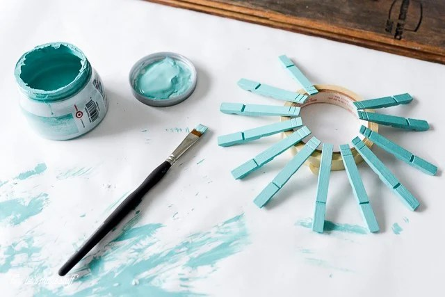 wooden clothespins being painted teal