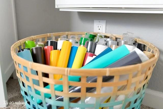 rolls of Cricut Vinyl in woven basket in craft room