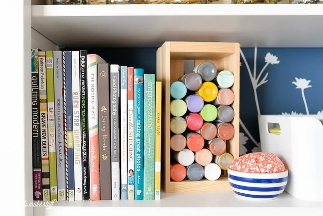 bookshelf with paint and books in craft room