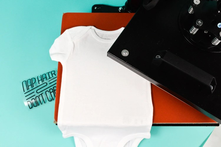 place your decal on your bodysuit, do a pre-press with the heat press for about 5 seconds.