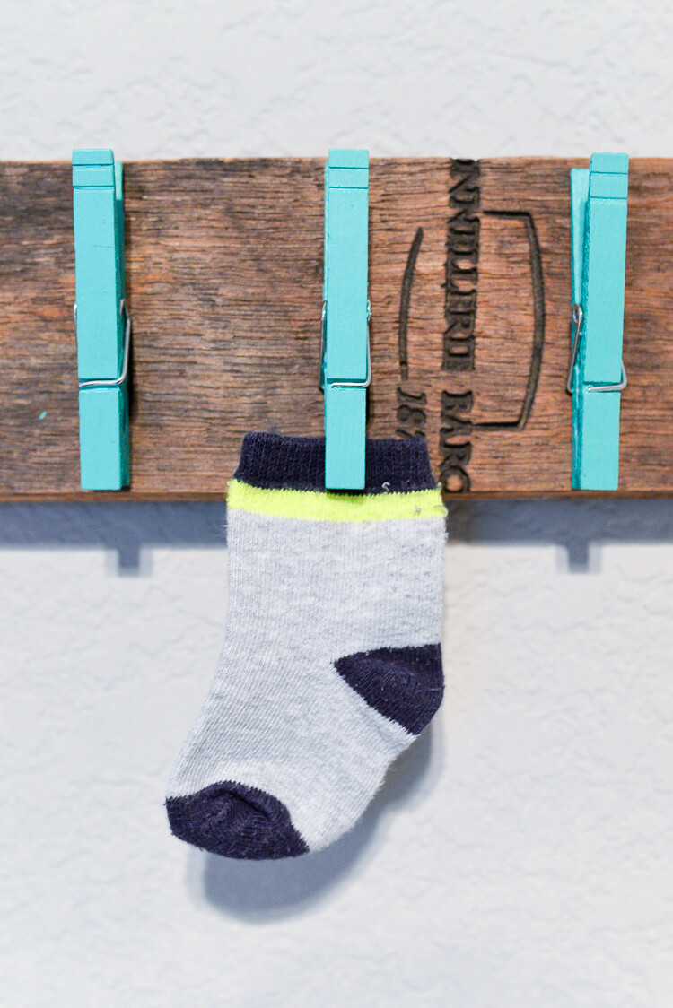 close up of DIY lost sock holder with clothespins and one baby sock