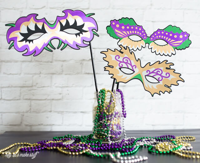 paper Mardi Grad masks in vase with Mardi Gras beads decorated