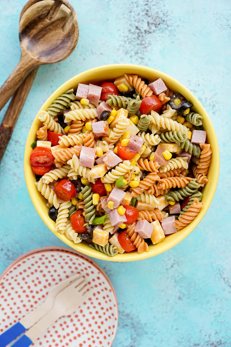 This easy summer pasta salad is perfect for barbecues and potlucks, with refreshing seasonal produce, flavorful ham and cheese, and a tangy dressing!