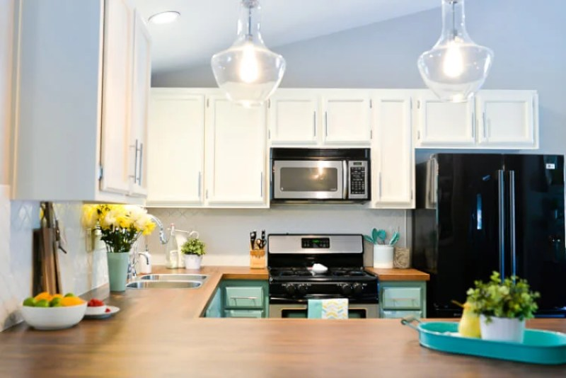 We totally transformed our dated 1980's kitchen with bright painted cabinets, new lighting, and gorgeous butcher block countertops. A gorgeous budget kitchen renovation!