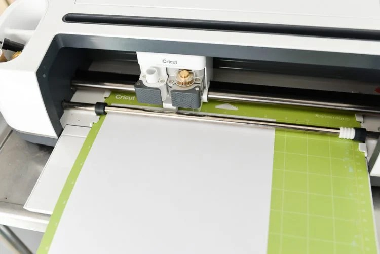 Mat inside the machine with white paper   There's so much to create using the Cricut Knife Blade. Here are 10 of my best Knife Blade tips to get it just right every time! You'll learn how to prep your mat, what to look for in Design Space, and other tricks for making the most of your Cricut Knife Blade.