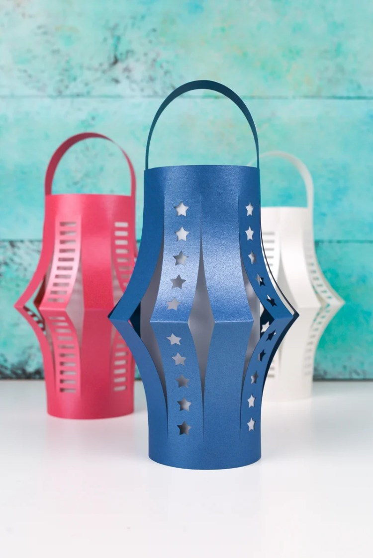 Get the free SVG cut files for these patriotic DIY paper lanterns! Delicate cut-outs made using your Cricut make these star-spangled lanterns a hit at any Fourth of July party.