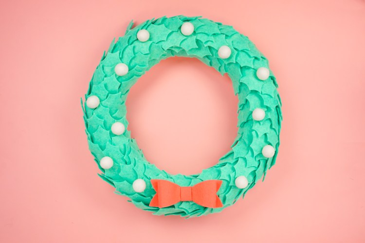 Use your Cricut Maker or Cricut Explore to make a beautiful felt wreath! This is an easy felt wreath DIY—just cut the leaves on your cutting machine, pin or hot glue, and add felt balls! A felt bow finishes this easy Christmas wreath.