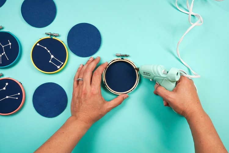 Add a ring of hot glue around the edge of the back of the hoop.