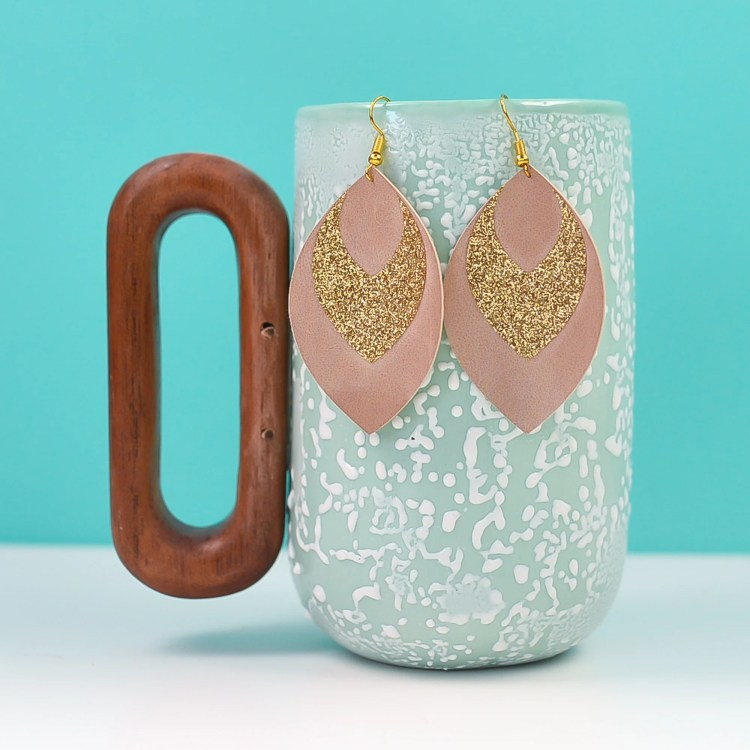 Glitter and suede Cricut earrings on a blue mug with a blue background.