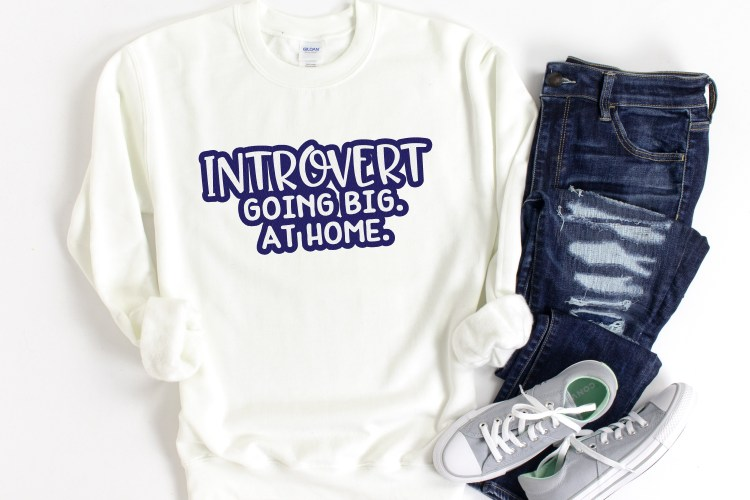 introvert SVG on a white sweatshirt with jeans and gray shoes