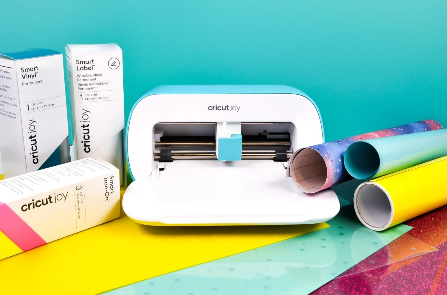 Cricut Joy surrounded by different materials.