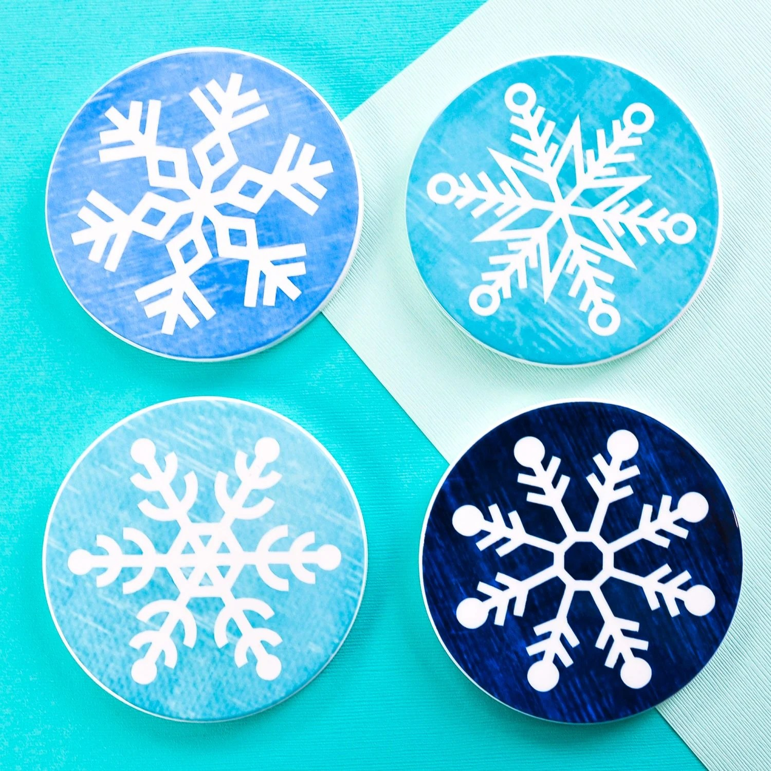 Four finished snowflake coasters on teal background