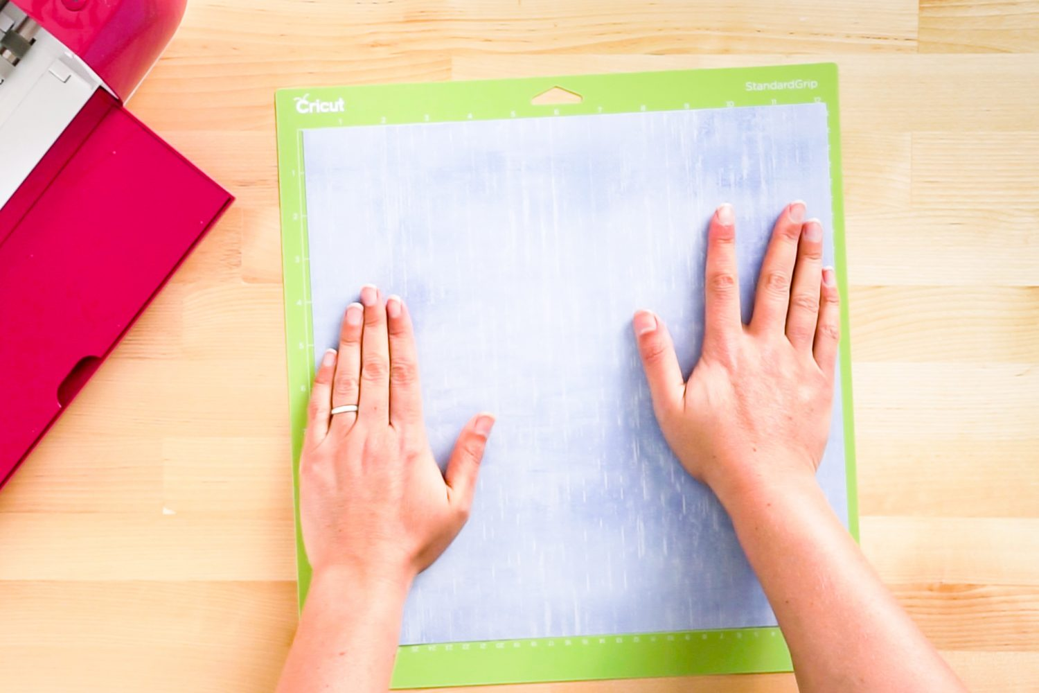 Hands putting Infusible Ink transfer sheet on a green cutting mat.