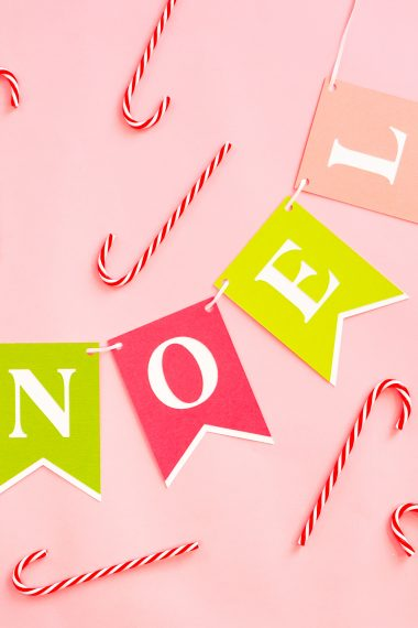 NOEL Banner on pink background with candy canes