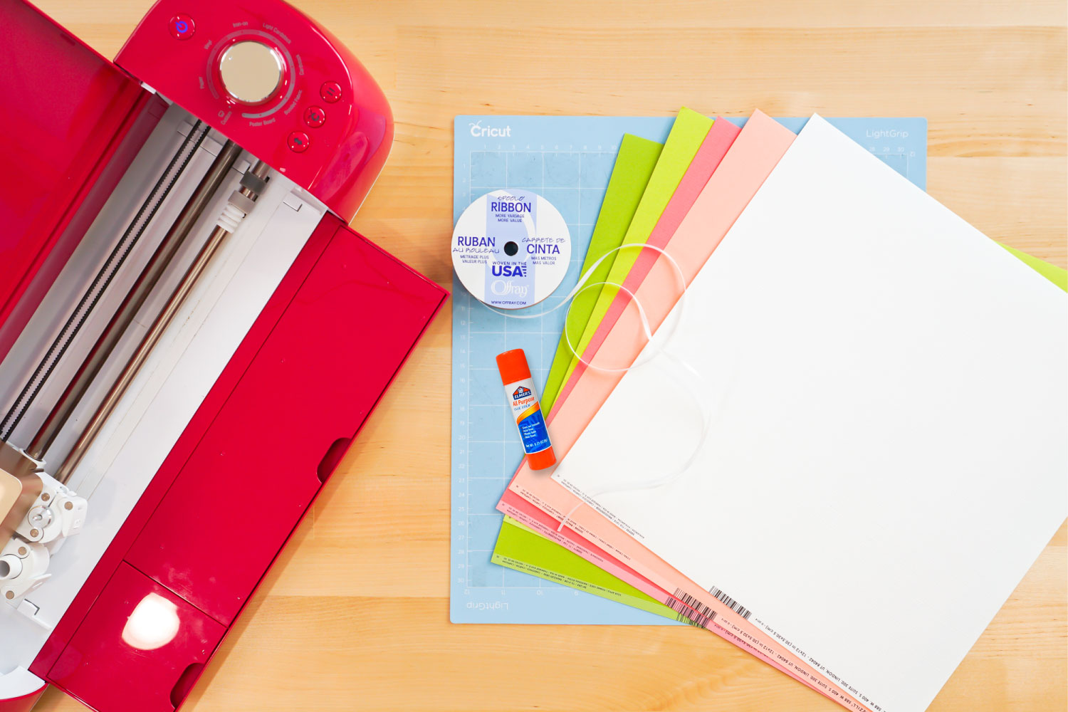 Supplies needed for the Christmas banner: Cricut, Cricut mat, five colors of cardstock, ribbon, glue stick