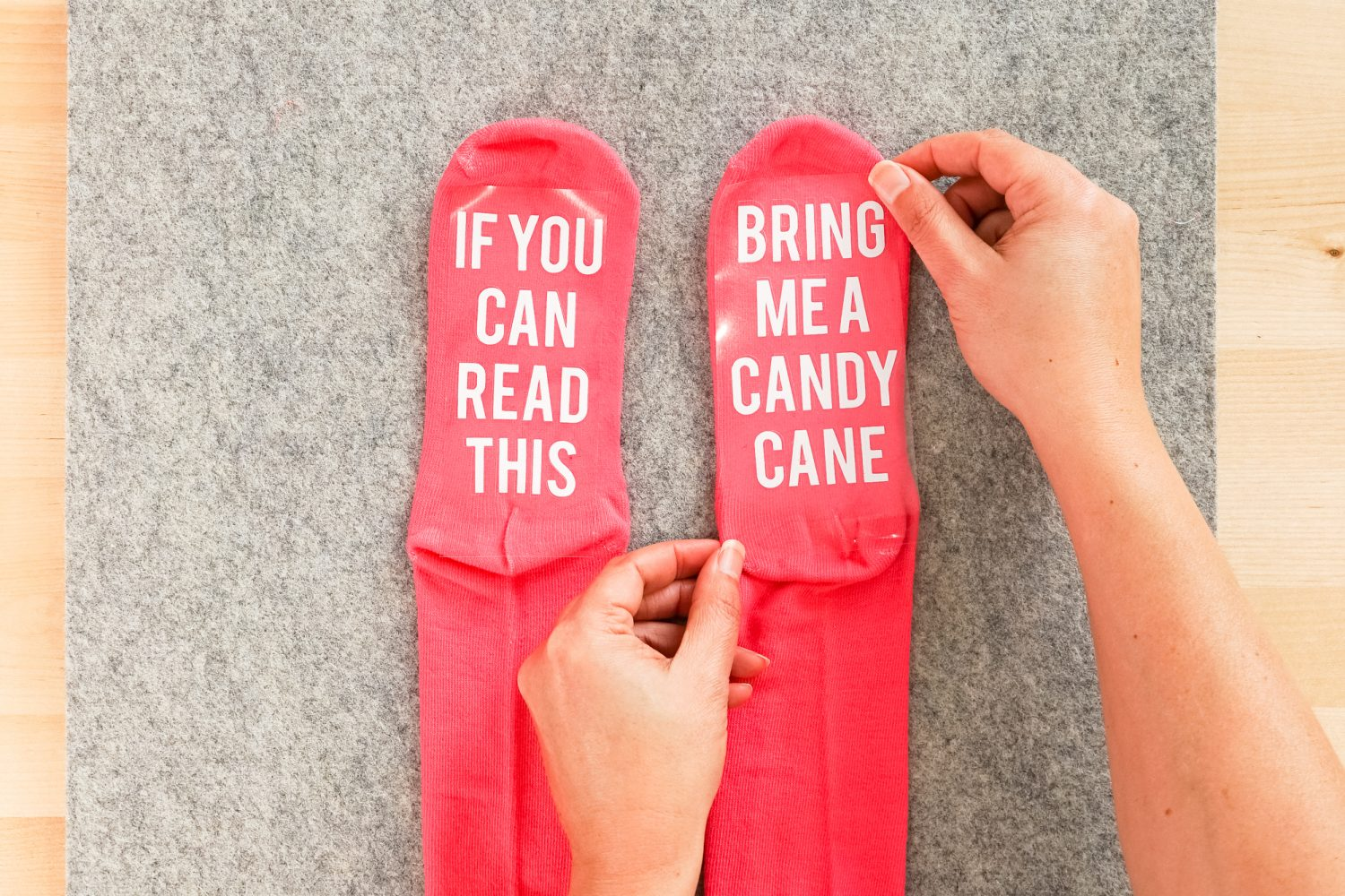 """Hands placing the """"bring me a candy cane"""" decal on the bottom of a pink sock."""