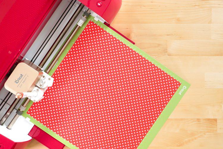 Cricut Explore cutting red polka dot paper.