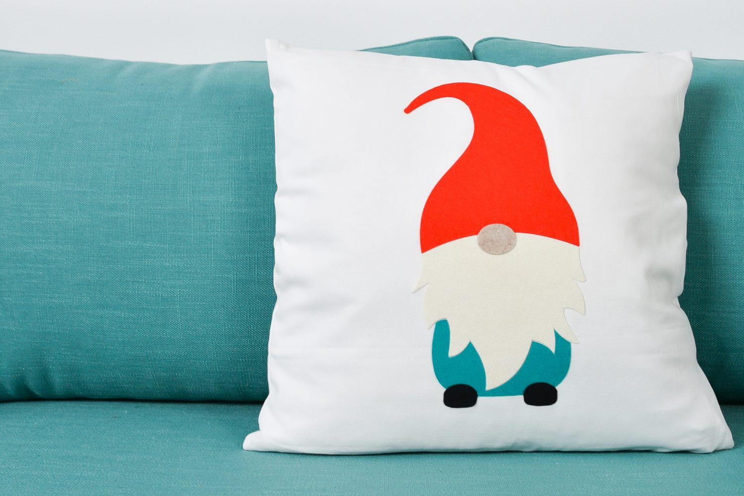 Finished gnome pillow sitting on a blue couch.
