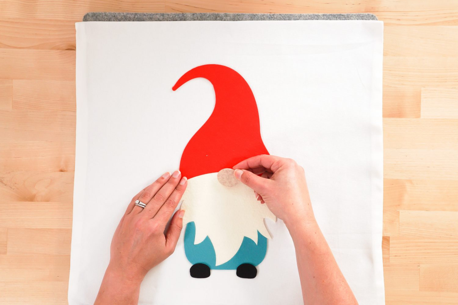 Hands placing all of the gnome pieces on the pillow.