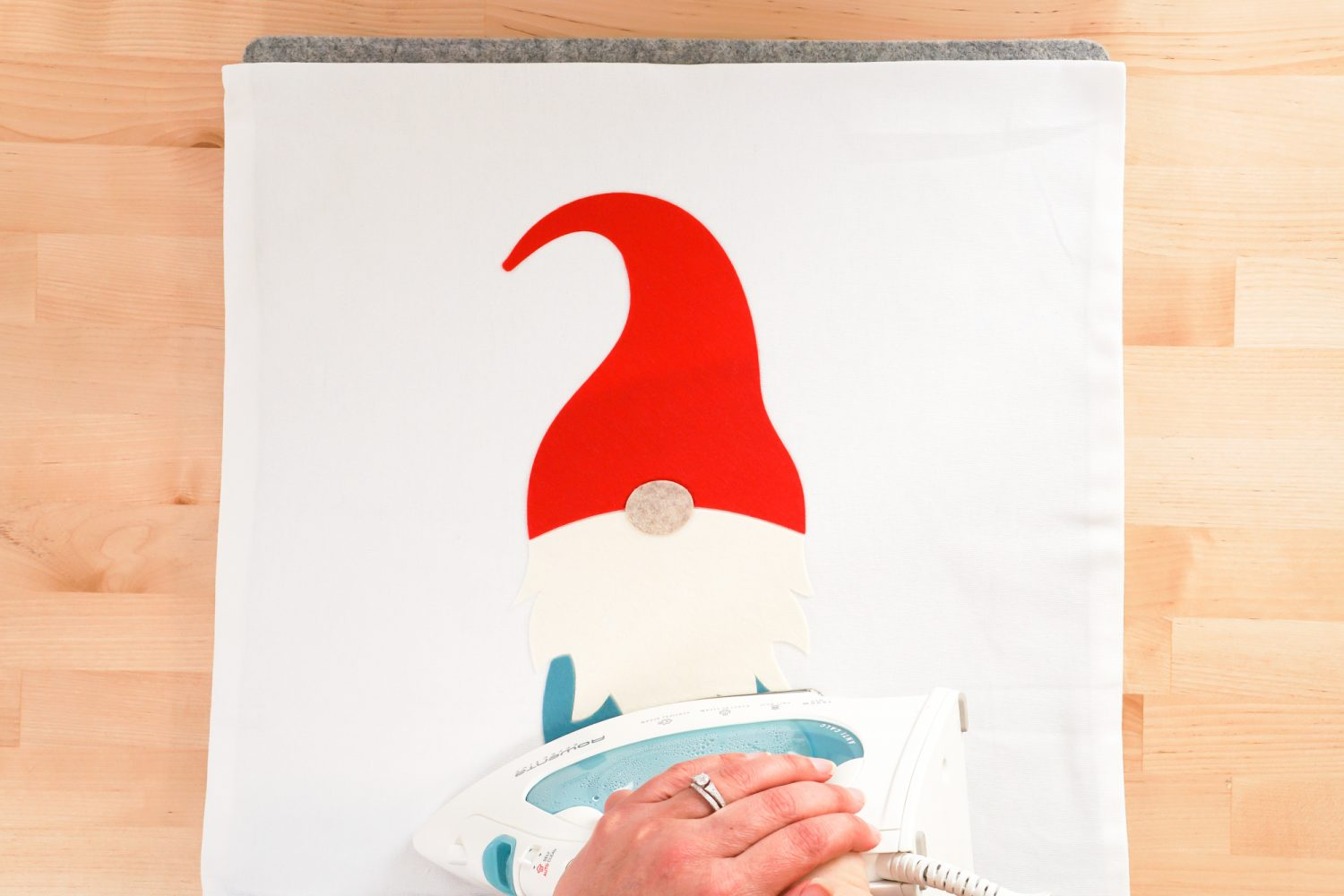 Hand pressing the gnome feet with a household iron.
