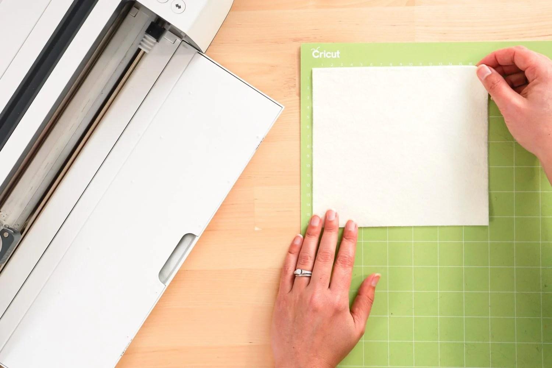 Hands placing the white felt on a Cricut mat.
