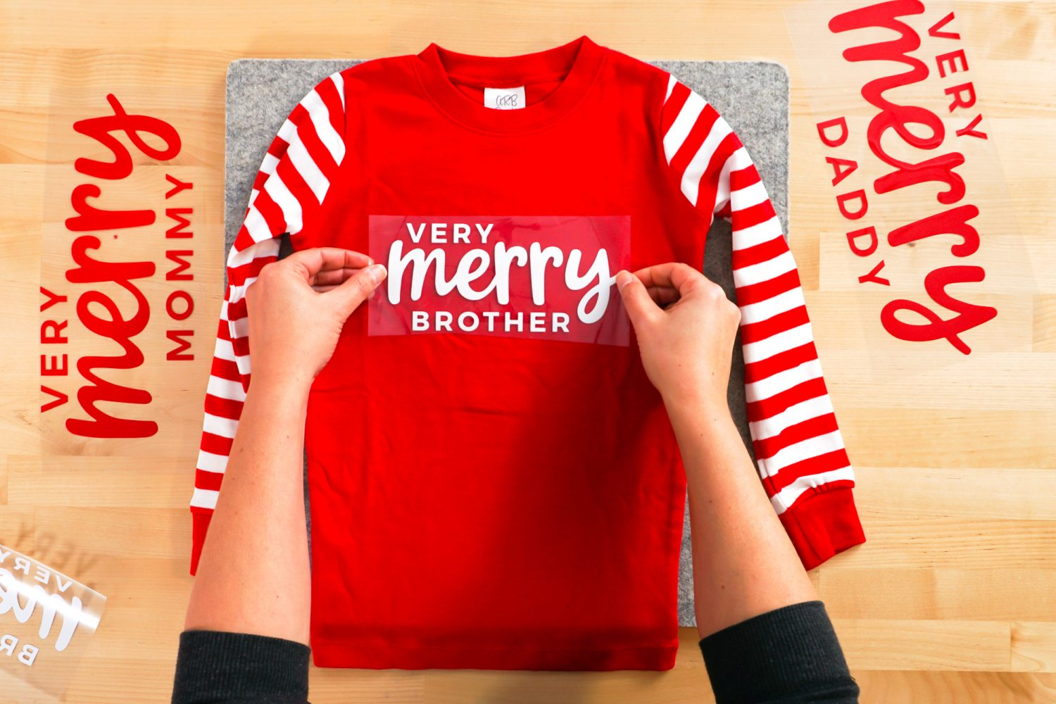 hands placing Very Merry Brother decal on shirt