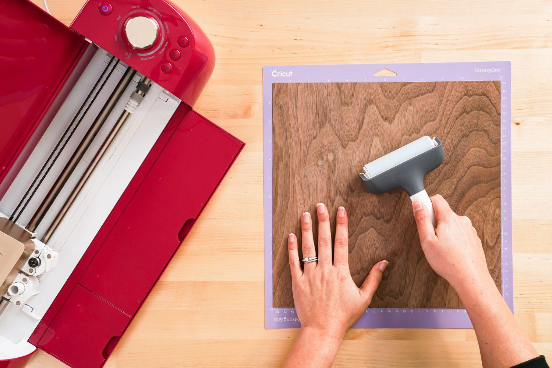 Hands using a brayer to place the veneer on a Cricut mat.