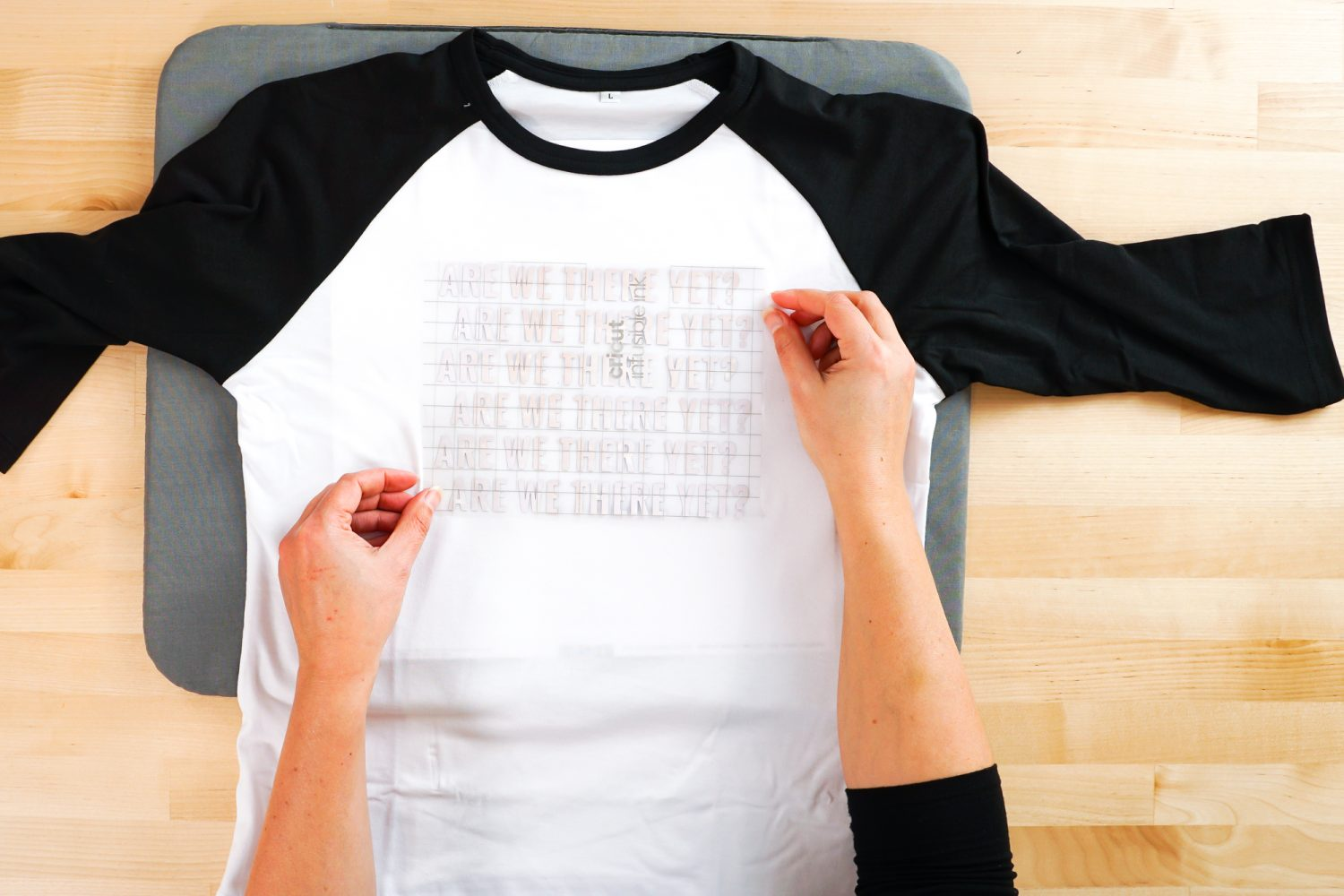 Hands placing the Infusible Ink decal on the raglan.