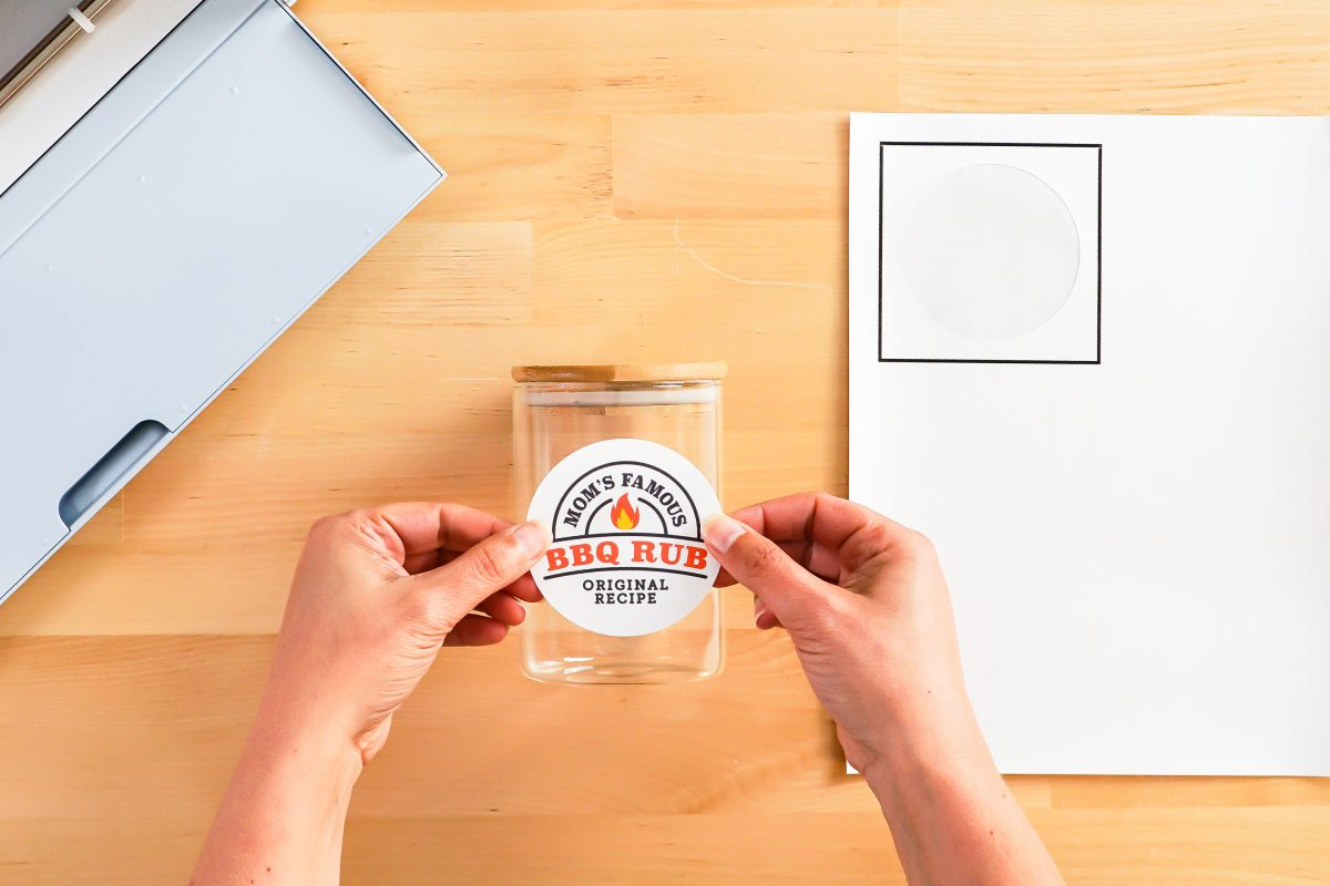 Hands placing sticker decal on jar