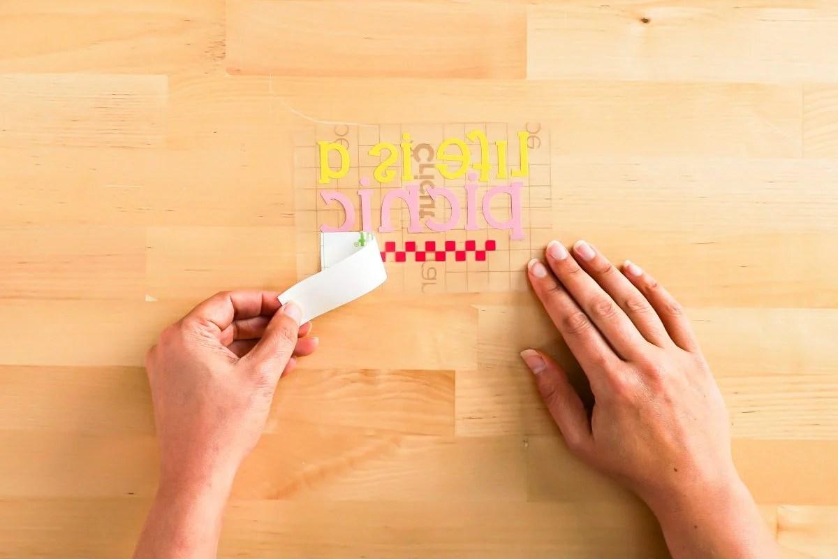 Hands peeling back transfer tape liner.