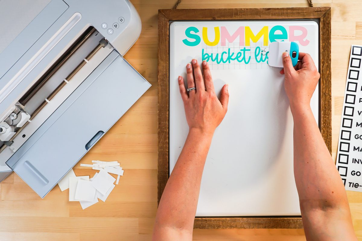 """Hands burnishing the words """"bucket list"""" to the white board."""