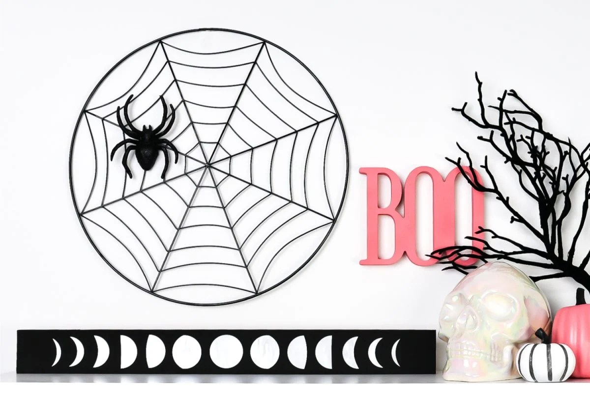 Moon phase artwork styled on a shelf with pink and black Halloween decor