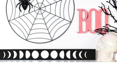 Moon artwork styled on a shelf with pink and black Halloween decor