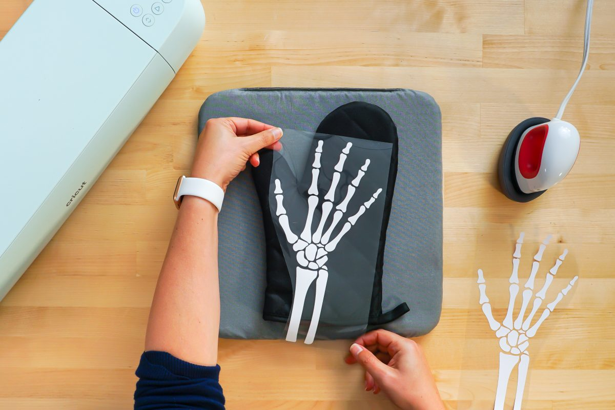 Hands placing iron on skeleton hand on black oven mitt with Cricut EasyPress Mini next to it.