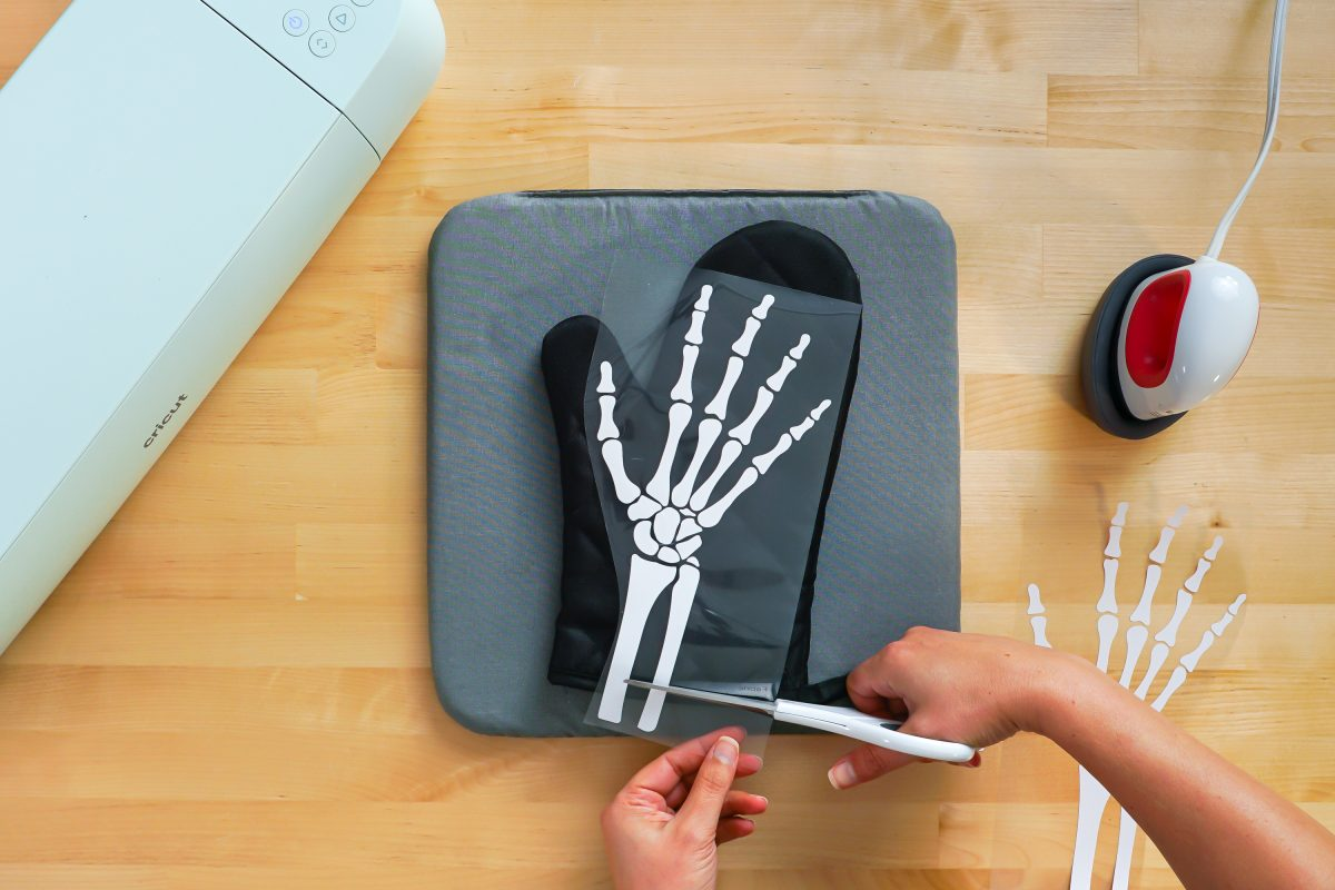 Hands cutting off the bottom of the iron on skeleton hand on black oven mitt.