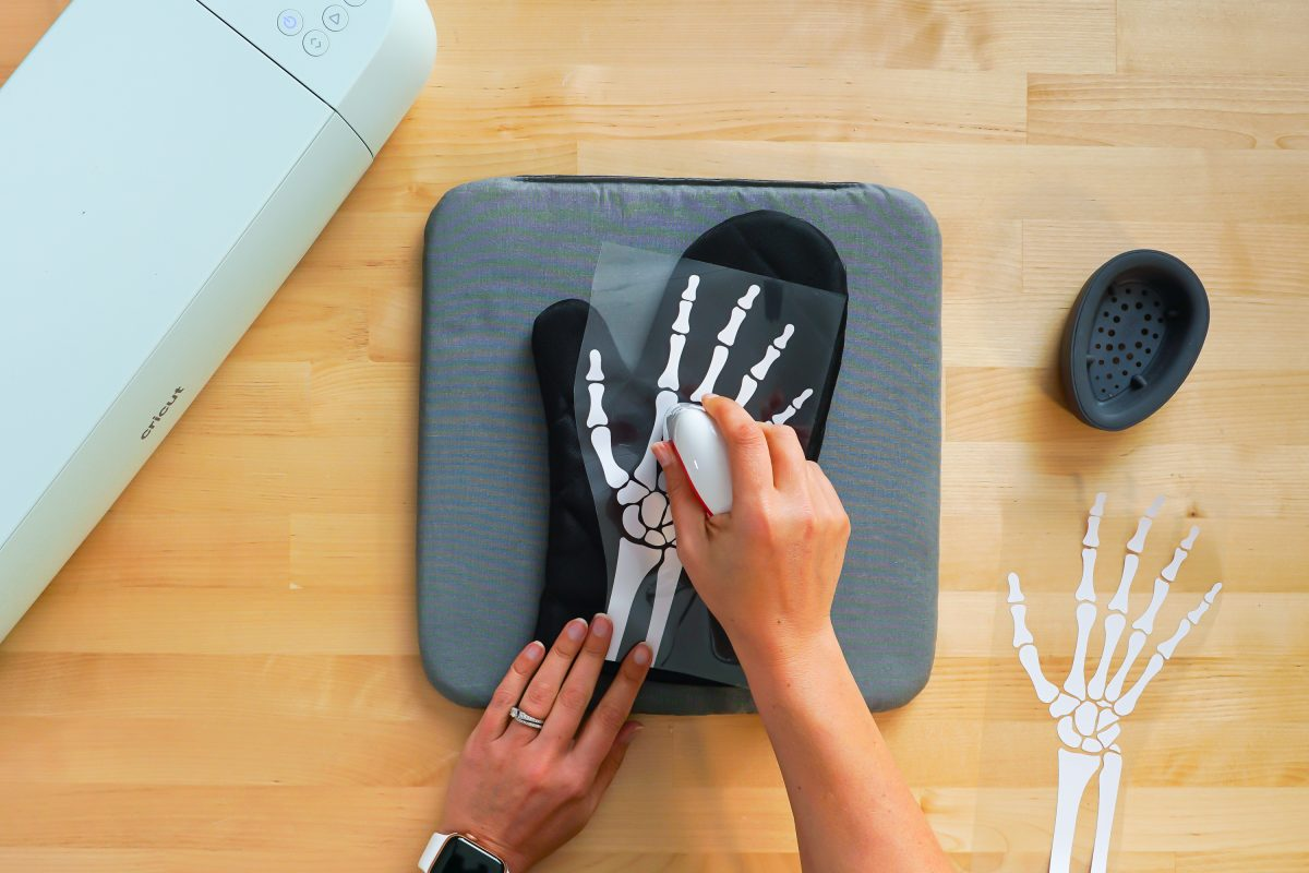Hands using the EasyPress Mini to adhere the iron on vinyl skeleton hand to the oven mitt.