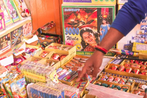A buyer pointing towards the fire crackers. During the Diwali season a variety of fire crackers come and sold in a day only.