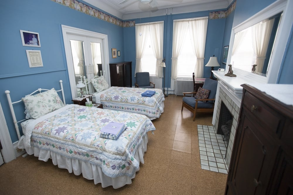 A quaint room with two twin beds and a fireplace
